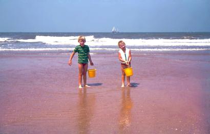 Oude dia foto van 40 jaar geleden. Een jongen en een meisje lopen over het strand, de horizon is weer recht. De foto is vrij van stof en beschadigingen. De kleuren zijn levendig. Fotobewerking / herstellen van oude foto's en dia's.