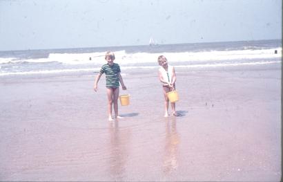 Oude dia foto van 40 jaar geleden. Een jongen en een meisje lopen over het strand, de horizon is scheef. Er zit stof en beschadigingen op de foto. De kleuren zijn flets. Fotobewerking / herstellen van oude foto's en dia's.