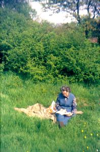 Oude dia foto van 40 jaar geleden. Een vrouw zit op een kleed in een grasveld, de foto is vrij van stof en beschadigingen. De kleuren zijn levendig. Fotobewerking / herstellen van oude foto's en dia's.