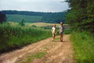 Oude dia foto van 40 jaar geleden. Een meisje en een jongen lopen over een zandweg, de foto is vrij van stof en beschadigingen. De zwarte balk is weggewerkt. De kleuren zijn levendig. Fotobewerking / herstellen van oude foto's en dia's.