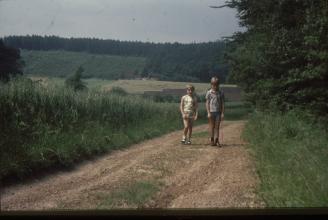 Oude dia foto van 40 jaar geleden. Een meisje en een jongen lopen over een zandweg, met stof en beschadigingen op de foto. Onderaan de foto loopt een zwarte balk. De foto is donker. Fotobewerking / herstellen van oude foto's en dia's.