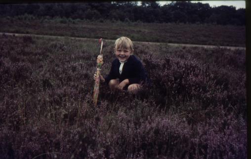 Oude dia foto van 40 jaar geleden. Een meisje met een paraplu in een veldje, met stof en beschadigingen op de foto. De foto is donker. Fotobewerking / herstellen van oude foto's en dia's.