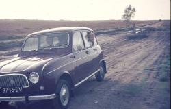 Oude dia foto van 40 jaar geleden. Een auto op een zandweg, met stof en beschadigingen op de foto. De kleuren zijn flets. Fotobewerking / herstellen van oude foto's en dia's.