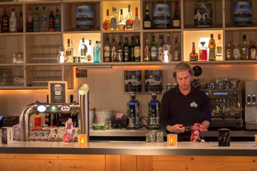 Foto van een barkeeper wie glazen aan t drogen is achter een bar. Links zijn meerdere Grolsch tappen zichtbaar. Commerciele fotografie.
