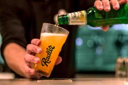 Foto van een barkeeper die een Grolsch Radler inschenkt in een Grolsch Radler glas. Commerciele fotografie.