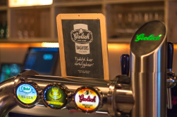 Foto van een bar met meerder biertappen met Grolsch erop. Een krijtbord met het Grolsch logo erop staat op de tap. Commerciele fotografie.