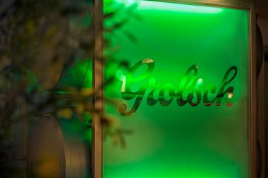 Foto in een bar met een glasplaat met het Grolsch logo erop. Er schijnt groen licht achter en er staat een plant links in beeld. Commerciele fotografie.