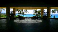 Foto genomen op Hawaii. Een loungeset in een hotellobby met een patroon van zonliht op de vloer. Palmbomen en een helderblauwe zee op de achtergrond. Natuurfotografie / landschapsfotografie.