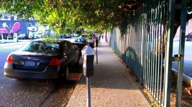 Foto gemaakt in Los Angeles. Een stoep met rechts auto's en parkeermeters, links een ijzeren hek en overhangende bladeren en takken van een boom. Stadslandschap / cityscape fotografie.