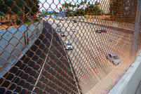 Foto gemaakt in Los Angeles. Auto's op een snelweg gefotografeerd vanaf een brug door een ijzeren hek. Stadslandschap / cityscape fotografie.