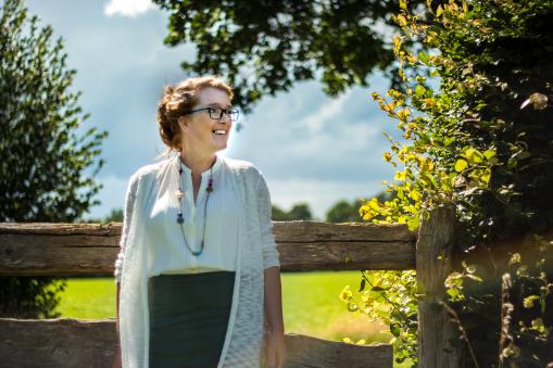 Fotoshoot op locatie van Myra. Ze leunt met haar rug tegen een hek, achter haar is een weiland. Portretfotografie / fotoshoot op locatie.