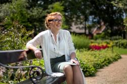 Fotoshoot op locatie van Myra. Ze zit op een bankje in een tuin. Portretfotografie / fotoshoot op locatie.