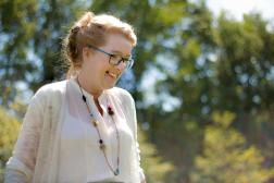Fotoshoot op locatie van Myra. Ze loopt door een tuin en kijkt lachend naar beneden. Portretfotografie / fotoshoot op locatie.