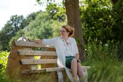 Fotoshoot op locatie van Myra. Ze zit op een bankje onder een boom. Portretfotografie / fotoshoot op locatie.