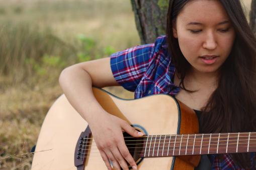 Fotoshoot op locatie van Sylvia. Ze zit met een gitaar onder de boom en kijkt ernaar. Portretfotografie / fotoshoot op locatie.