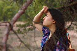 Fotoshoot op locatie van Sylvia. Ze staat onder een boom en houdt haar hand voor haar ogen tegen de zon. Ze kijkt omhoog. Portretfotografie / fotoshoot op locatie.