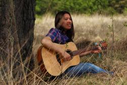 Fotoshoot op locatie van Sylvia. Ze zit met een gitaar onder een boom en kijkt lachend uit beeld. Portretfotografie / fotoshoot op locatie.