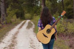 Fotoshoot op locatie van Sylvia. Ze is van achter gefotografeerd. Ze heeft een gitaar op de rug, en loopt weg van de camera over een bosweg. Portretfotografie / fotoshoot op locatie.