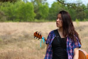 Fotoshoot op locatie van Sylvia. Ze heeft een gitaar op de rug en staat onder de tak van een boom. Ze kijkt naar links. Portretfotografie / fotoshoot op locatie.