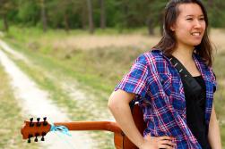 Fotoshoot op locatie van Sylvia. Ze staat met een hand in haar zij, gitaar op de rug. Lachend kijkt ze naar rechts. Portretfotografie / fotoshoot op locatie.