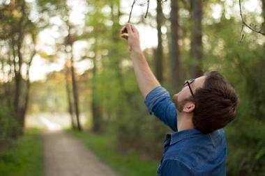 Fotoshoot op locatie van Twan. Hij kijkt omhoog en grijpt naar een tak. Portretfotografie / fotoshoot op locatie.