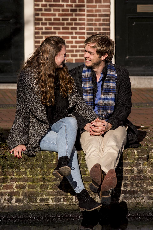 Fotoshoot op locatie van Coen en Daphne. Ze zitten op de rand van de gracht, en kijken lachend naar elkaar. Portretfotografie / fotoshoot op locatie.