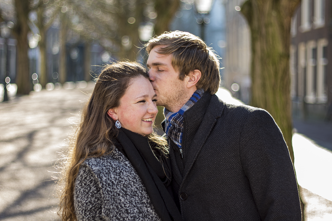 Fotoshoot op locatie van Coen en Daphne. Het is zonnig en Coen geeft Daphne een kus op haar hoofd, Daphne lacht. Portretfotografie / fotoshoot op locatie.