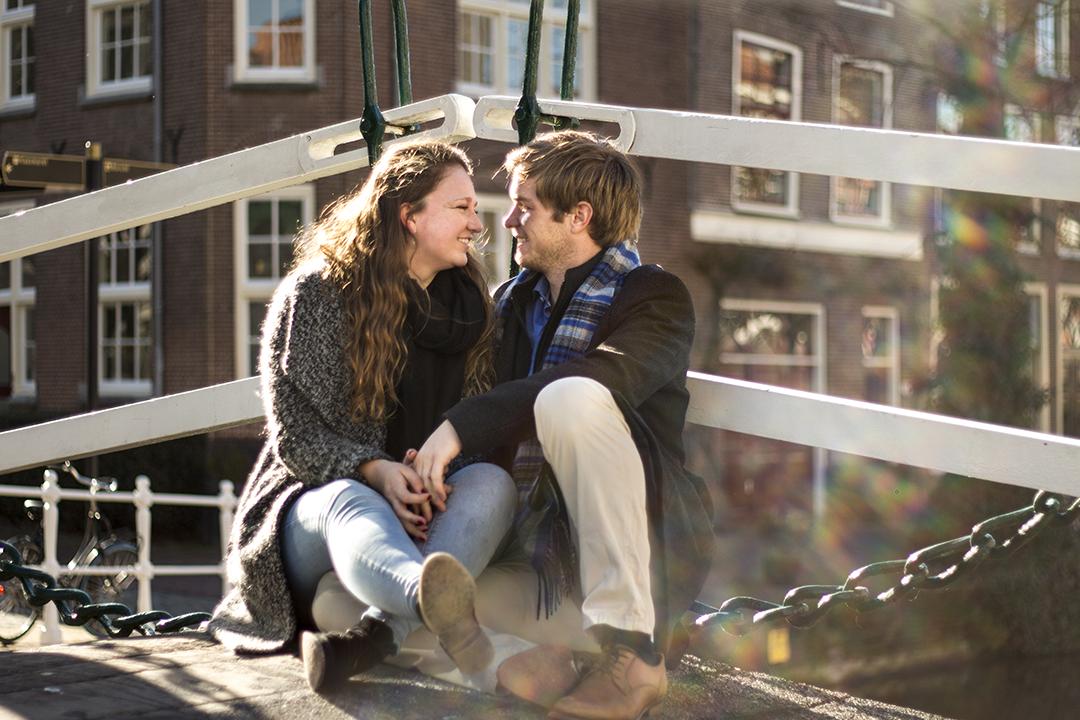 Fotoshoot op locatie van Coen en Daphne. Ze zitten op een brug en kijken elkaar lachend aan. Er loopt een lensflare rechts door het beeld. Portretfotografie / fotoshoot op locatie.