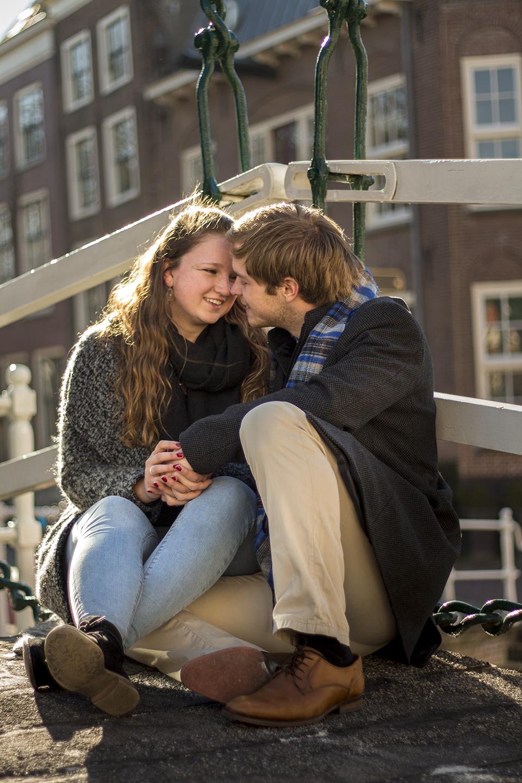 Fotoshoot op locatie van Coen en Daphne. Ze zitten op een brug, en staan op het punt elkaar een kus te geven. Portretfotografie / fotoshoot op locatie.