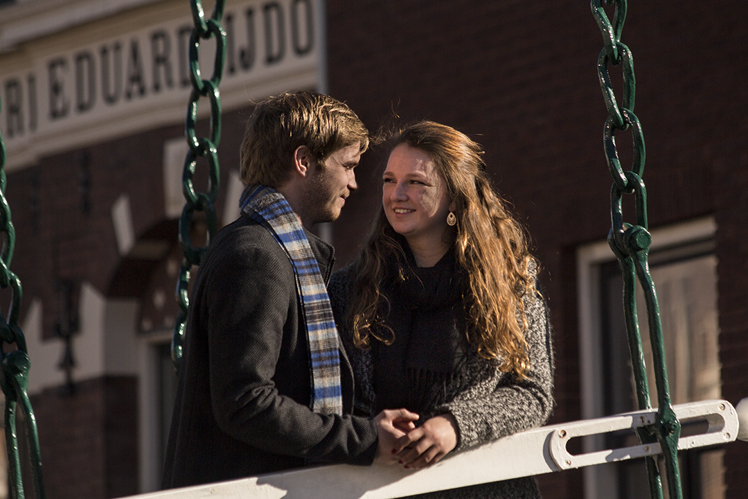 Fotoshoot op locatie van Coen en Daphne. Ze staan op een brug en kijken elkaar verliefd aan. Portretfotografie / fotoshoot op locatie.